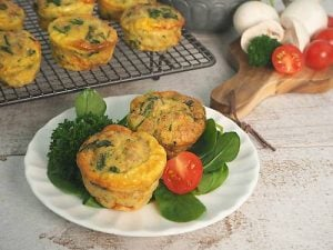 Egg and Meat muffins on white plate with salad